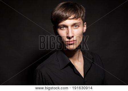 Portrait of male model on black background in studio photo. Expression and style
