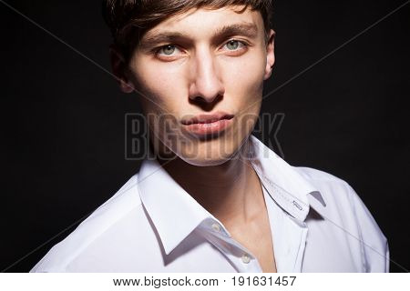 Portrait of male model in white shirt on black background in studio photo. Style and fashion. Cool attractive guy