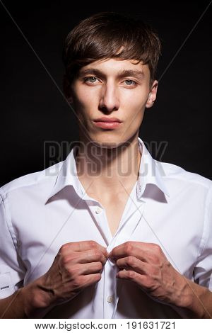 Attractive man in white shirt on black background in studio photo. Style and fashion. Cool attractive guy