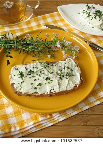 Herb curd with cuckoo flower on bread