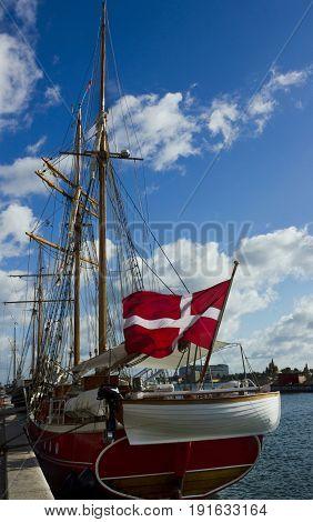 Yacht with Danish flag berthed in Copenhagen port.
