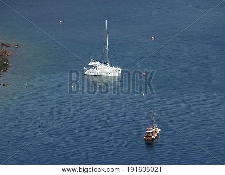 Deep blue Aegean sea with boats seen from Santorini Island, Greece