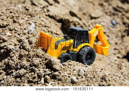 Construction machinery toys in the black sand in sunny day. Construction or transportation process concept, selective focus, close up.
