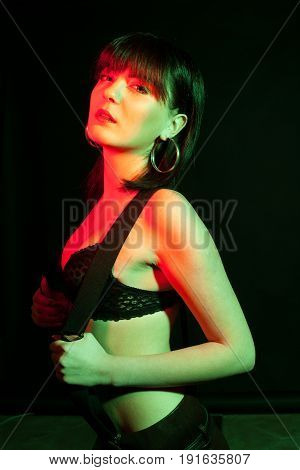 Woman wearing lingerie in red and green light. Studio photo. Hot brunette wearing suspenders