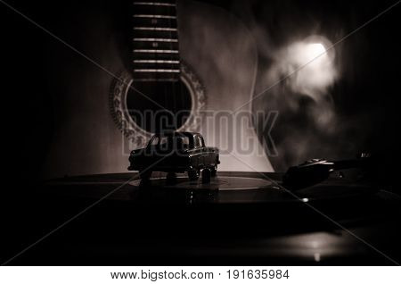 Vintage Vinyl Record Playing On Player And Acoustic Guitar On Background With Fire Orange Smoke. Blu