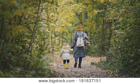 Young mother and her daughter little girl walking in a autumn park, telephoto