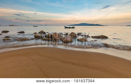 Looking out over the south china sea in Nha Trang bay just after sunset with fishing boats, large rocks and a sandy beach in the foreground.