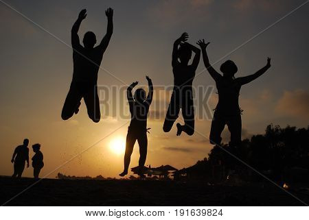 Family jumping on a beach at sunset. Happy family on the sea. Summer vacation concept