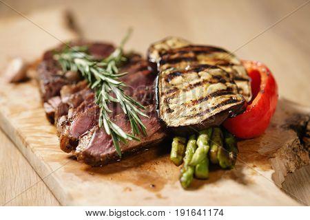 sliced medium rib eye steak with grilled vegetables, shallow focus