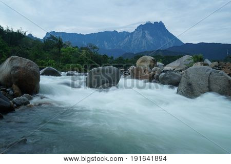 Melangkap river with silky water,rocky bottom and with Mount Kinabalu at the background