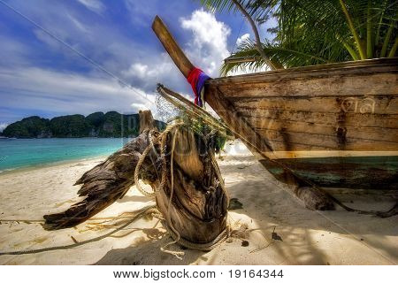Old Thai boats on the tropical beach. Andaman sea. Phi Phi Don island. Kingdom Thailand