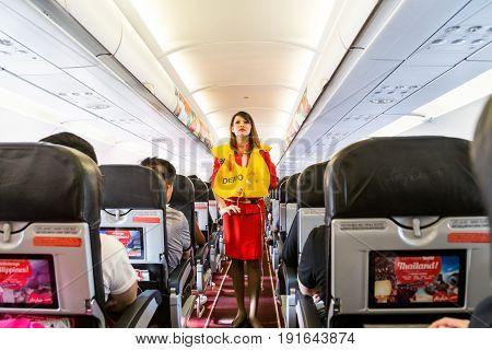 Kuala Lumpur, Malaysia, June 8, 2017: Airasia Hostess Demonstrate Safety Procedures To Passengers Pr