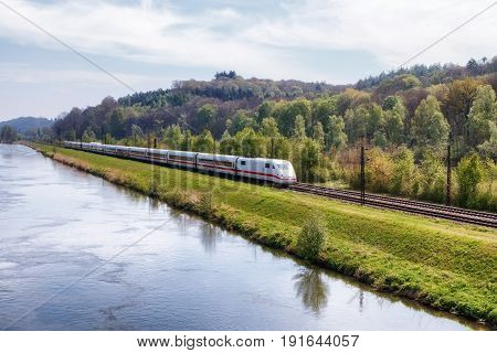 REISENSBURG GERMANY - MAY 6 2017: German high-speed train ICE (Intercity-Express) on the banks of the Danube river on May 6 2017 in Reisensburg Germany.