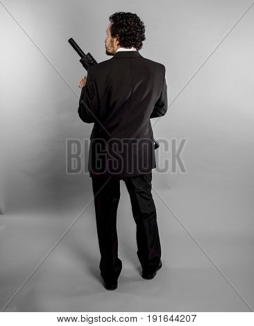 Guard Businessman in black suit and armed with machine gun on gray background
