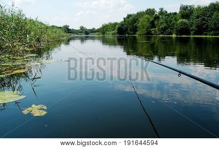 Fishing Rod On The Background Of Smooth Water Surface At Noon.