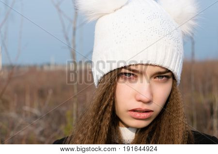 sad young beautiful girl in a white hat