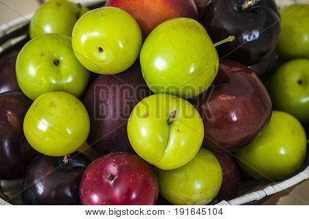 Red japanese plum and green sour plums in basket