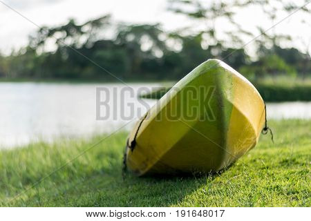Bright green and yellow fiberglass canoe on shore at forest lake