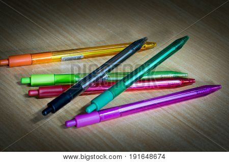 Many Bright colored Ballpoint pens on wooden desk.