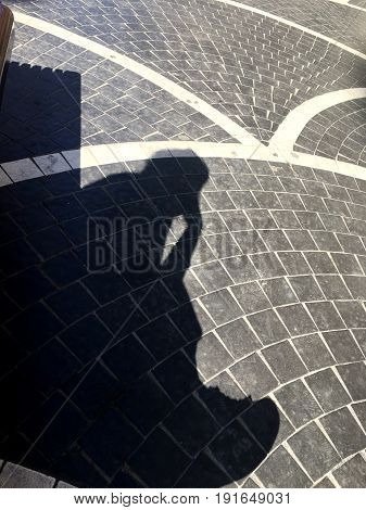 Stone street with a shadow of a woman. The girl on the bench. The shadow of the girl.