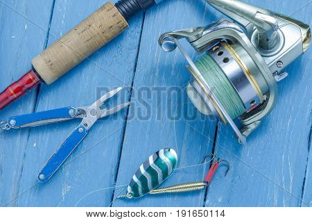Spinning, Reel, Fishing Green Spoon And Pliers. The Bait And The Tool Of A Fisherman.
