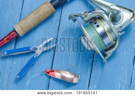 Spinning, Reel, Yellow-red Fishing Spoon And Pliers. The Bait And The Tool Of A Fisherman.