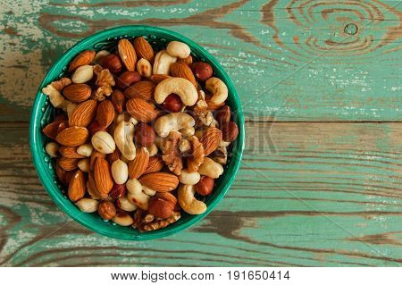 Mixed Nuts In A Turquoise Bowl On A Turquoise Wooden Background.