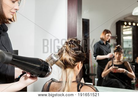 Woman at hairdresser salon getting a new hairstyle. Professional service. New hairstyle. Stylist at work