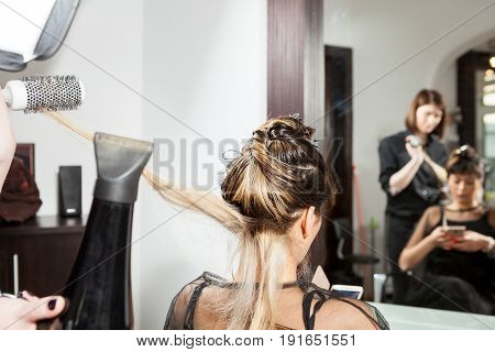 Woman at hair salon getting a new hairstyle. Professional service. New hairstyle. Stylist at work