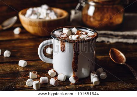 Cocoa Mug with Marshmallows. Jar of Cocoa Powder and Marshmallow Bowl on Backdrop.