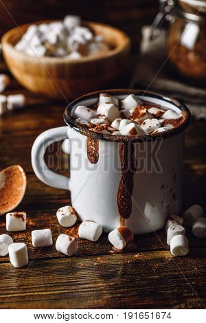 Cocoa Mug with Marshmallows. Jar of Cocoa Powder and Marshmallow Bowl on Backdrop. Vertical Orientation.