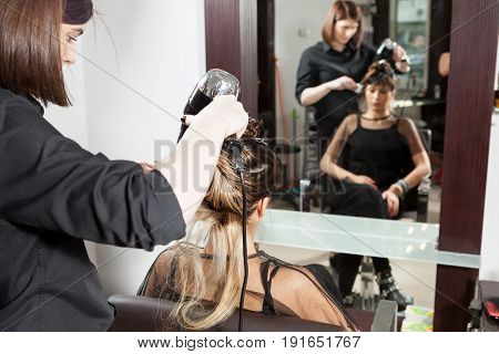 At the hair salon getting a new hairstyle. Professional service. New hairstyle. Stylist at work
