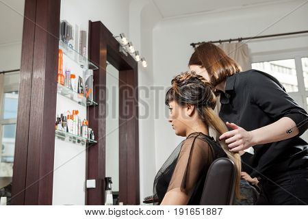 Woman at the hair salon getting a new hairstyle. Professional service. New hairstyle. Stylist at work