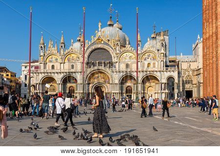 Venice, Italy - May 18, 2017: Tourists are walking around the Basilica di San Marco on the Piazza San Marco (St. Mark's Square). This is the main square of Venice.