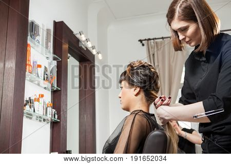 Beautiful woman at the hair salon getting a new hairstyle. Professional service. New hairstyle. Stylist at work