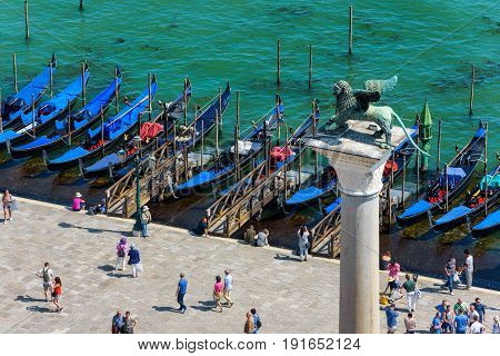 Venice, Italy - May 18, 2017: The famous column with winged lion on the San Marco Embankment. Piazza San Marco or St Mark's Square with gondolas. The lion is the symbol of Venice.