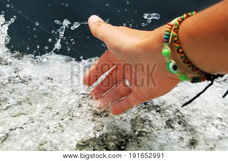 Female Hand Touching Splashes Of Foaming Water While Floating On Engine Boat.