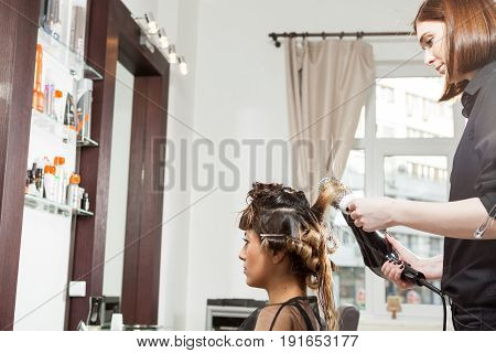 Woman at the hair salon getting a hairstyle. Professional service. New hairstyle. Stylist at work