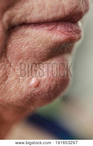 Details of senior woman face. Elderly pensioner female chin and lips close up.