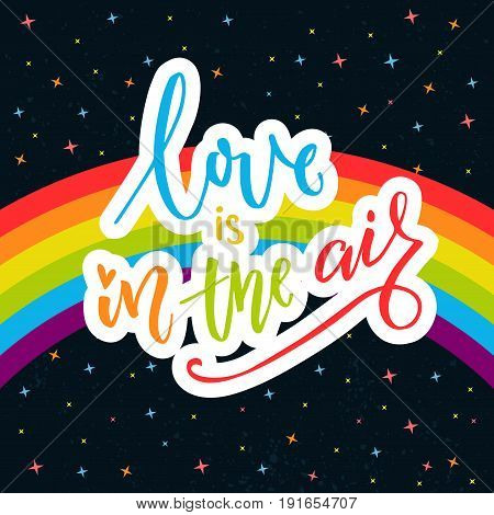 Love is in the air. Words on rainbow parade flag at dark sky with stars. Gay pride saying for stickers, t-shirts and posters