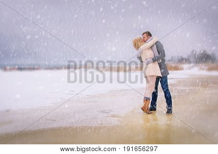 Romantic lovely couple kissing in the snowy nature.
