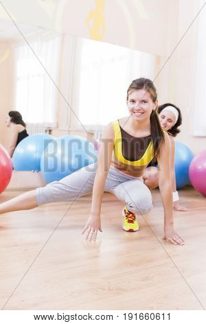 Sport Fitness Healthy Lifestyle Concepts.Two Female Caucasian Athletes in Good Fit Posing With Fitballs in Sport Gym.Vertical Image Composition