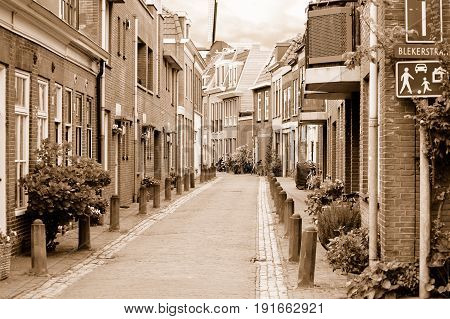 View of a small cosy side street in Haarlem in overcast spring day. Sepia toned image.