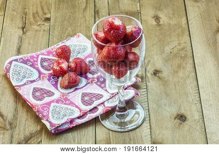 Berry strawberries in a glass fouger on a wooden surface