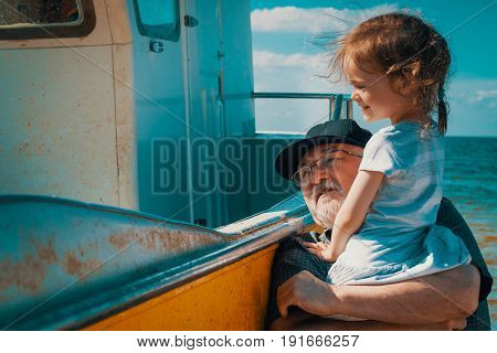 Grandfather fisherman shows his granddaughter's boat on the beach in summer