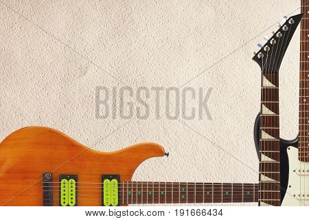 Mahogany and black electric guitars and neck on the rough cardboard background with plenty of copy space.