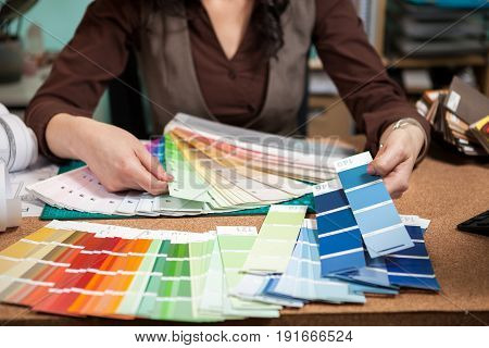 Close up architect with color palette on her desk. Working on new architect and design plan. Professional architecture blueprints