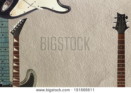 Black and grey electric guitars and two necks on the rough cardboard background with plenty of copy space.