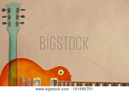 Honey sunburst electric guitar and neck on the rough cardboard background with plenty of copy space.