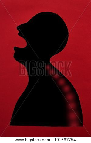 concept of human disease and pain localization on silhouette - abstract man with sharp pain in the spine, open mouth, isolated on red background, top view, flat lay